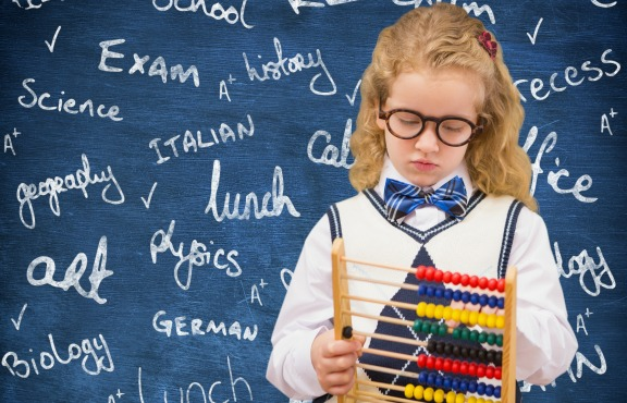 Digital composite image of schoolgirl holding abacus against chalkboard